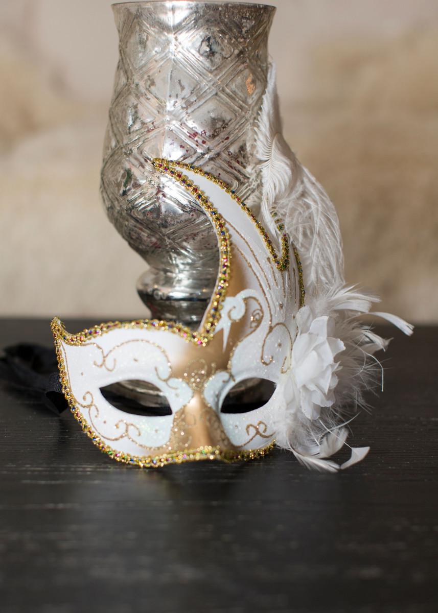 Mardi Gras mask with silver urn candle holder on my black coffee table