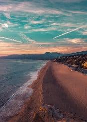 beach water ocean sea sand sky clouds trails