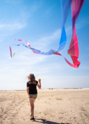 beach sand kite wind girl person flying sky strap tail sun summer blur focus