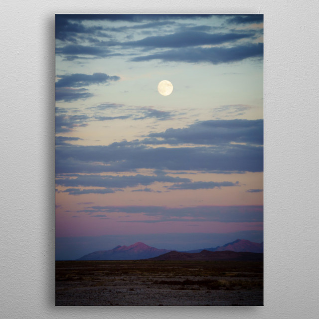the moon rises over mountains in the desert. metal poster