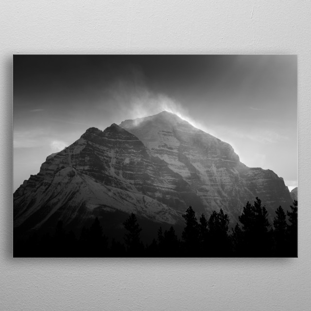 A view of Mt. Temple in the distance as gusts of wind hurl snow high off its peaks into the air. Shot taken from the Lake Louise Ski Resort. ... metal poster