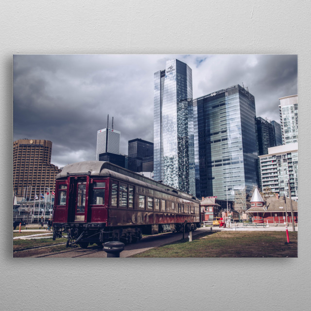 Tall, cool-toned skyscrapers of Toronto's finance district reflect a gloomy sky. At their feet, an ancient train car from another era. This p... metal poster