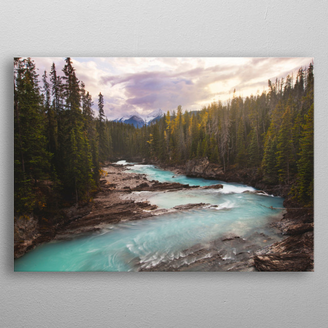 A stunning alpine river in Canada with mountains in the distance and a beautiful sunset overhead. metal poster