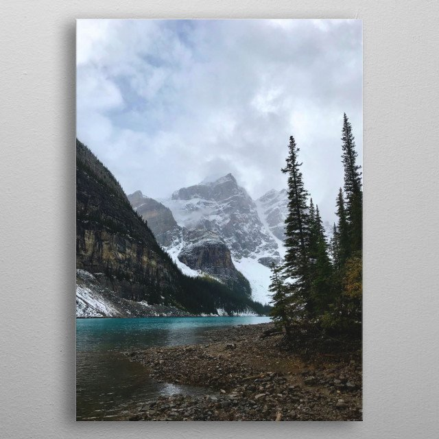 A beautiful lake with turquoise water is nestled against an alpine forest and a backdrop of moody mountains wreathed in snow and clouds. metal poster