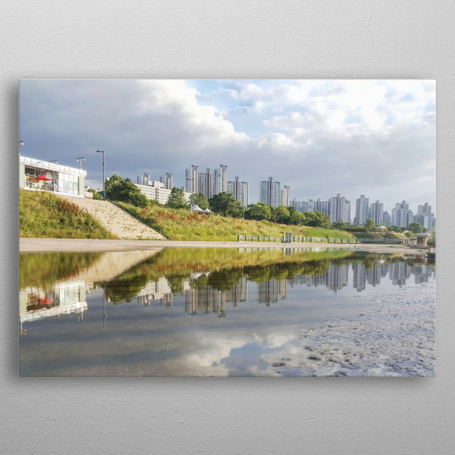 A small water pond creates a perfect reflection of the Seoul Skyline and all the skyscrapers. metal poster