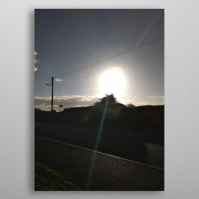 Bight sun outlining a dark and shadowed road. metal poster