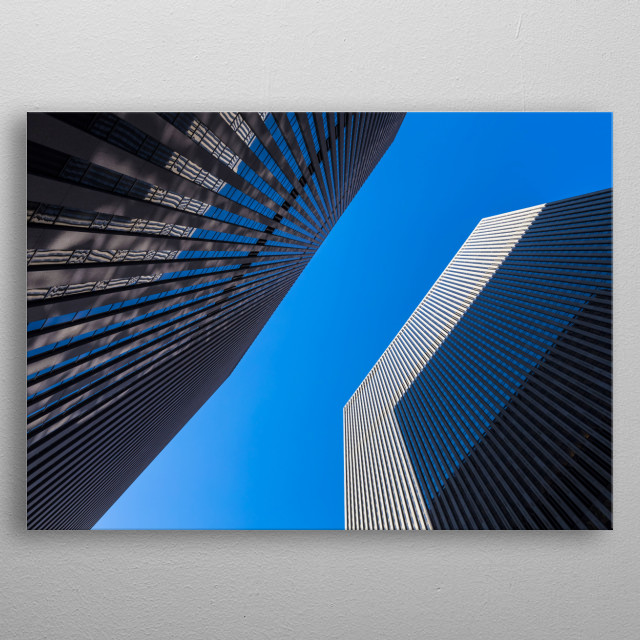 New York City - Upward view of two skyscrapers in Manhattan. One skyscraper casts a shadow onto the other one. metal poster
