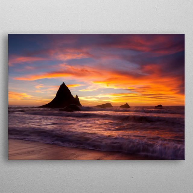 A beautiful blue, orange and pink sunset over the ocean with rocky islands jutting from water up towards the sky. metal poster