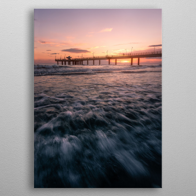 The light of the sunset burning behind the pier in Marina di Pietrasanta, Tuscany metal poster