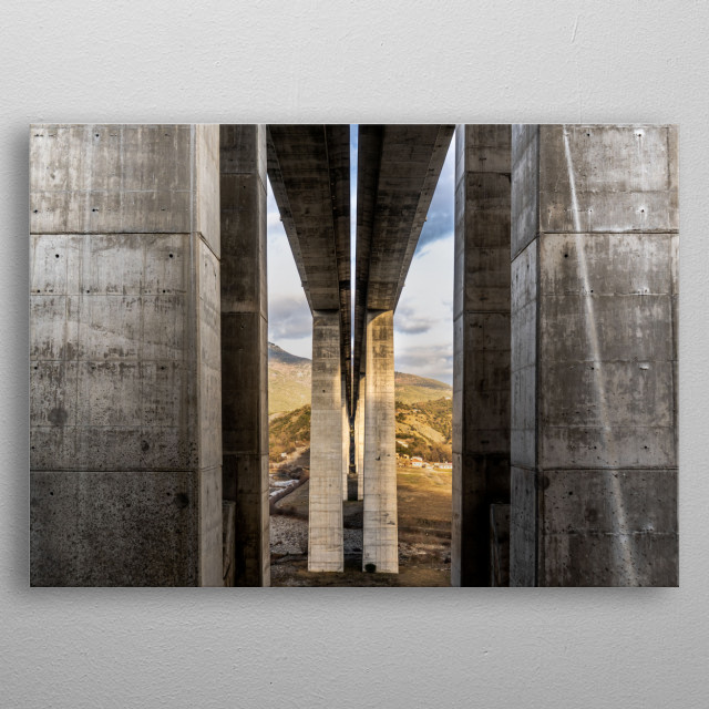 A photograph under a massive highway bridge passing over a valley metal poster