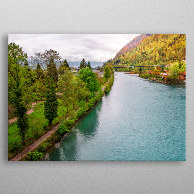 Aerial shot by a drone flying over the Lake Thun in Interlaken, Switzerland. Colorful landscape showing a curve of the lake and vegetation. metal poster
