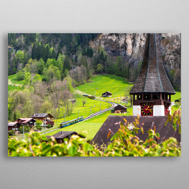 Amazing landscape in Lauterbrunnen, Switzerland. View of the top of a church and a train on the rail. metal poster