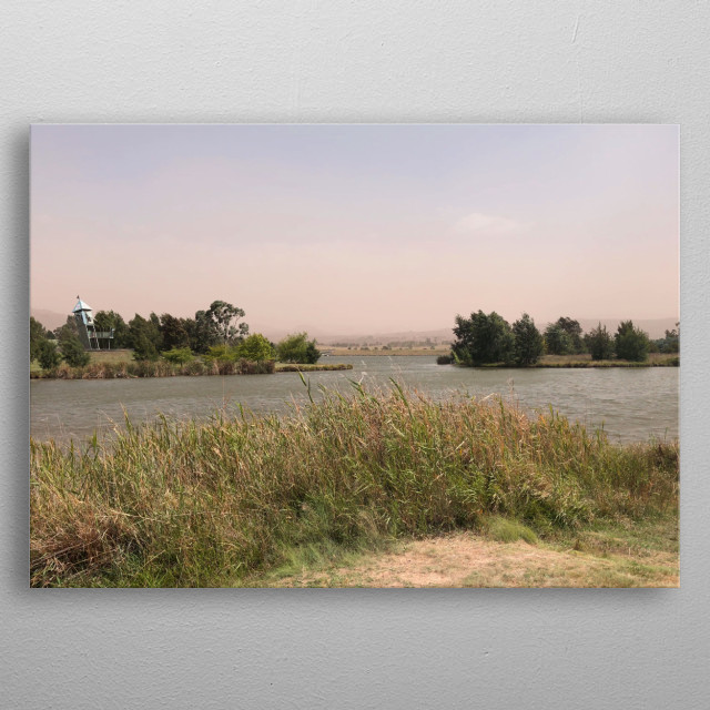 Dust builds in the distance, on this warm windy afternoon by the lake. metal poster