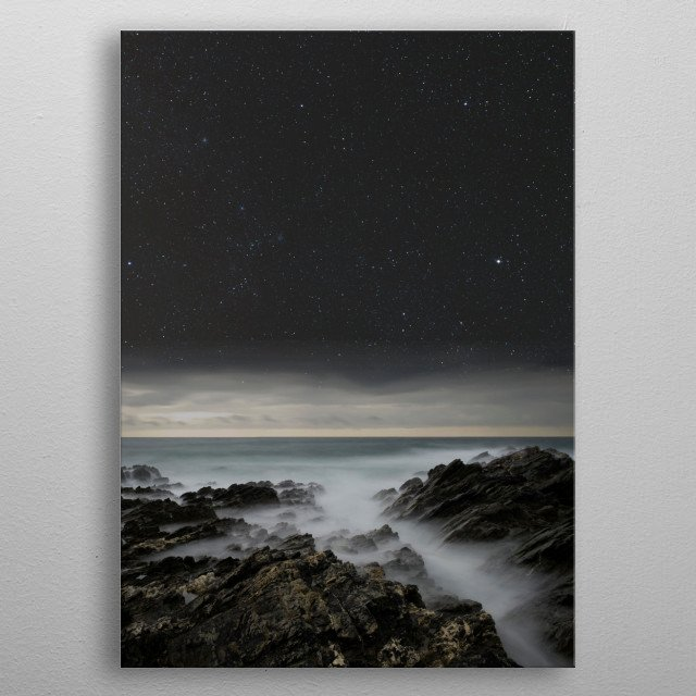The rocky Cornish coastline at night. metal poster