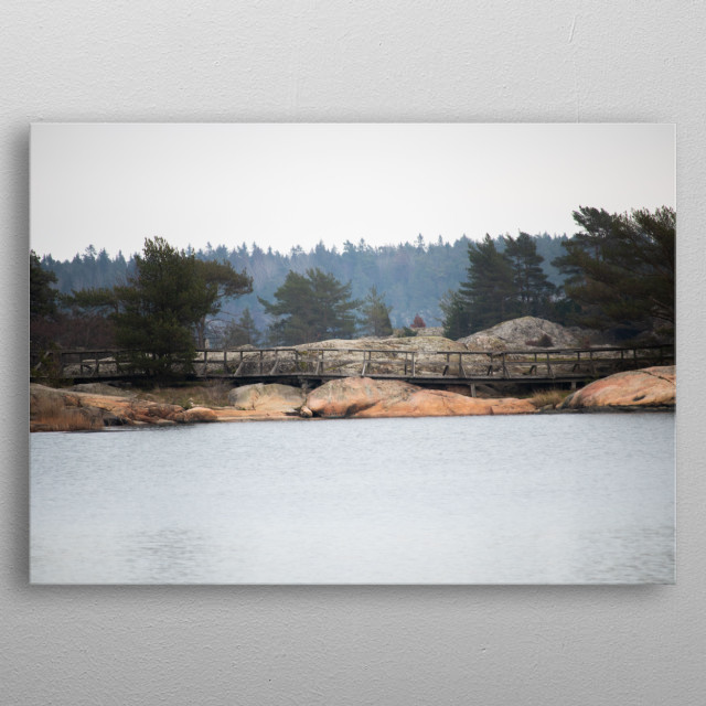 A bridge spanning some cliffs along the waters edge on a hazy day in September. metal poster