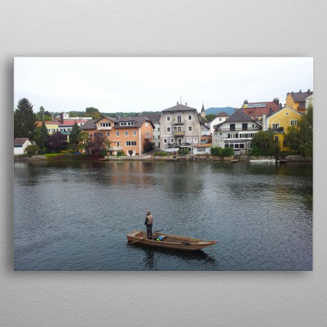 A fisherman at a boat in a lake in Austria. A line of colorful buildings along the lake. metal poster