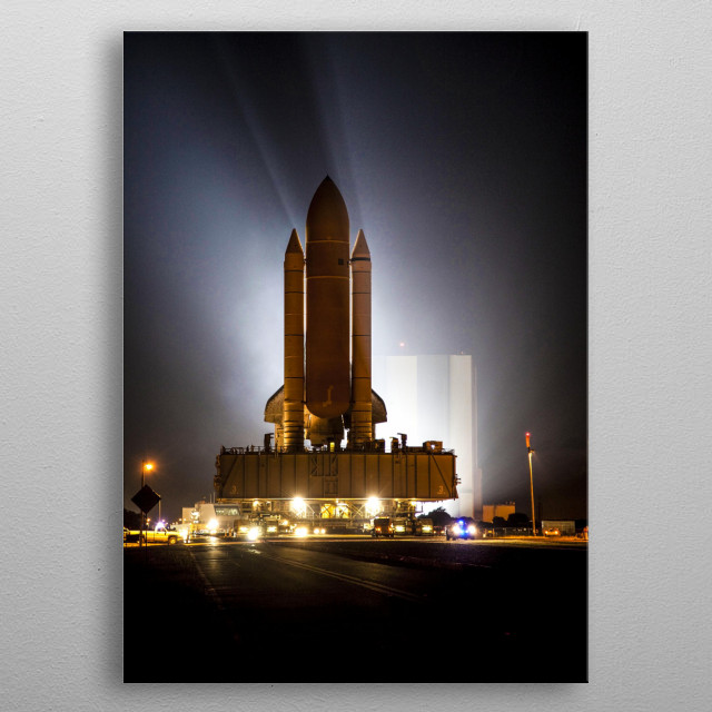 CAPE CANAVERAL, Fla. -- Bathed in xenon lights, space shuttle Atlantis embarks on its final journey from the Vehicle Assembly Building to La metal poster