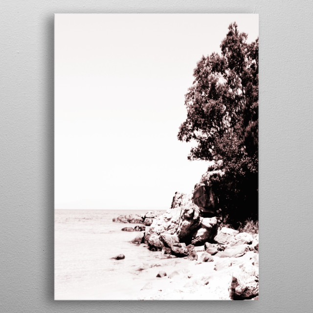 Monochrome capture of a beautiful beachscape with rocks and trees. metal poster