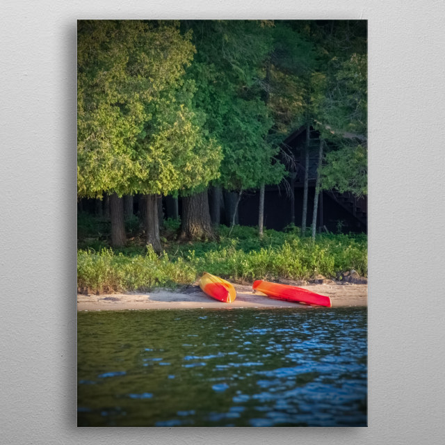Two bright red - orange kayaks lie on the sandy beach of a lake. Green trees line the shore. Light reflects off ripples on the water.  metal poster