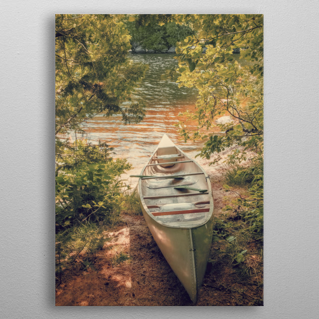 A canoe sits in a clearing between trees with green leaves by the shore of a lake in New York State. Green and brown nature photography.  metal poster