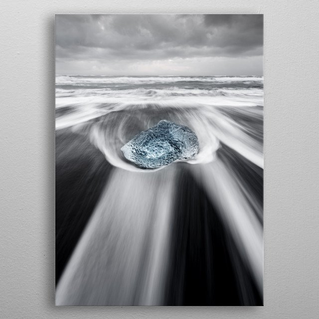 Large block of ice in blue shades on a beach with strong surf, the water movement can be seen, above a contrasting gray cloudy sky metal poster