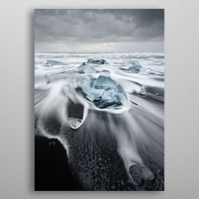 Large blocks of ice in blue shades on a beach with strong surf, the water movement can be seen, above a contrasting gray cloudy sky metal poster