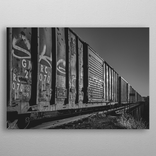 A long train of battered box cars traveling across the bridge make a interesting perspective. Black and white photography by Bob Orsillo metal poster