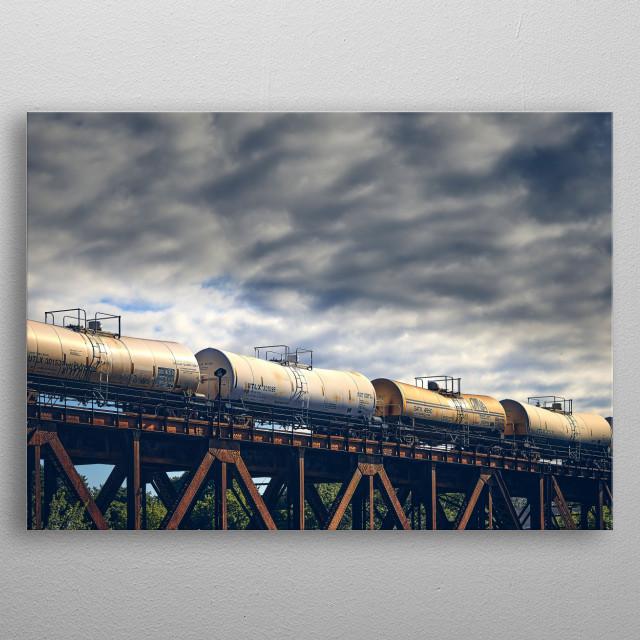 Train pulling a line of liquid cargo tank cars cross over a railroad bridge. Photography by Bob Orsillo metal poster