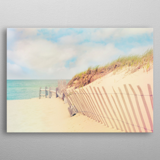 A sand fence at Crosby Landing Beach in Brewster, Massachusetts leads down the beach to the ocean. The sky is blue with fluffy white clouds. metal poster